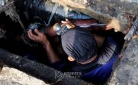 Masuk ke Gorong-Gorong, Pasukan Biru Bersihkan Lumpur di Kawasan Gambir