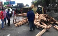Truk Bermuatan Kayu Terguling di Tol Tomang Arah Tangerang