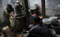 Petugas Pertamina Bantu Bersihkan Sumur Air Warga Terdampak Kebakaran Kilang Cilacap