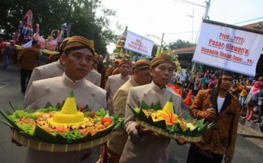 Pedagang membawa gunungan dan tumpeng saat mengikuti prosesi Boyongan Pedagang di Pasar Klewer, Solo, Jawa Tengah, Jumat (21/4/2017). Prosesi boyongan pedagang tersebut digelar sebagai rangkaian peresmian Pasar Klewer oleh Presiden Joko Widodo.
