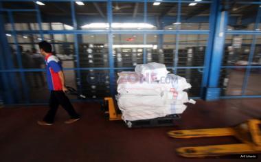 """Pekerja membawa paket barang sesuai daerah yang akan dikirim melalui udara di gudang logistik kawasan Bandara Soekarno-Hatta, Tangerang, Banten, Kamis (18/5/2017). Menurut asosiasi pelaku jasa kurir dan logistik, pengiriman logistik di musim Ramadan dan Lebaran 2017 akan mengalami peningkatan hingga lima puluh persen dibanding tahun sebelumnya, seiring meningkatnya transaksi belanja """"online"""" atau """"e-commerce."""""""