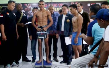 Petinju asal Indonesia Tibo Monabesa (kiri) dan petinju Filipina Arnold Garde (kanan) saat timbang berat badan di GOR Cendrawasih, Cengkareng, Jakarta Barat, Jumat (19/5/2017). Kedua petinju akan melakukan laga dalam Kejuaraan WBC Internasional yang akan dilaksanakan pada 20 Mei 2017 dalam 12 ronde.