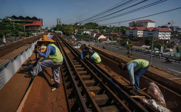 Pekerja menyelesaikan penggantian bantalan rel kereta api di Jembatan Kleringan, Kota Baru, DI Yogyakarta, Kamis (18/5/2017). Perawatan dan pengecekan rutin rel kereta api tersebut guna menjamin keselamatan perjalanan kereta api serta mencegah amblasnya bantalan rel.