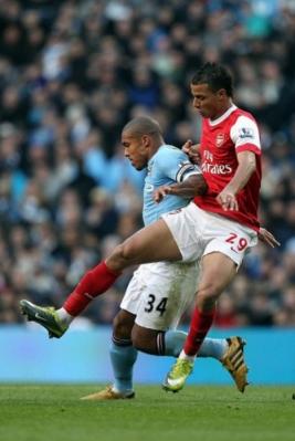 Penyerang Arsenal Marouane Chamakh berduel dengan Nigel De Jong