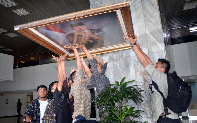 Sejumlah mahasiswa yang tak puas audiensi dengan Pimpinan DPR terkait kenaikan Bahan Bakar Minyak (BBM) melakukan aksi di pelataran depan Gedung Nusantara III DPR dengan menurunkan bingkai foto Presiden Susilo Bambang Yudhoyono (SBY), Jakarta.