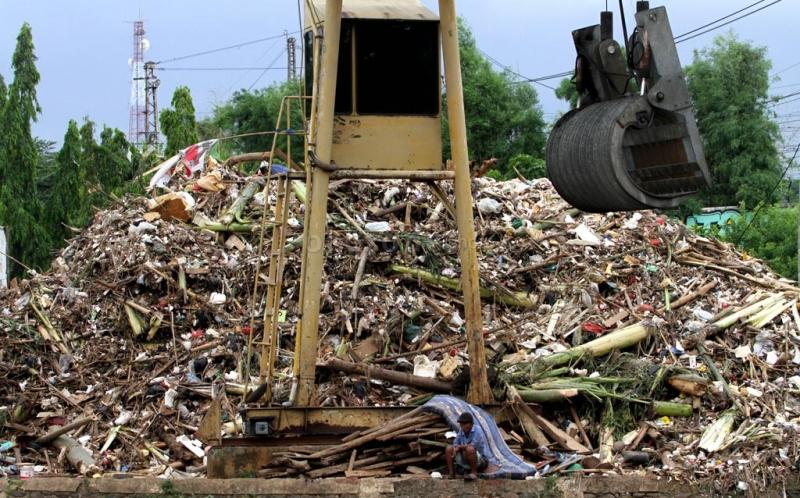 Seseorang duduk di depan tumpukan sampah yang menggunung di Pintu Air Manggarai, Jakarta Selatan, Minggu (23/12/2012). Pengerukan sampah di Pintu Air Manggarai merupakan pekerjaan rutin yang dilakukan petugas Dinas Pekerjaan Umum Pemprov DKI Jakarta, terlebih di saat musim penghujan. Ini dilakuan agar aliran air ke pintu air tidak terganggu oleh tumpukan sampah.
