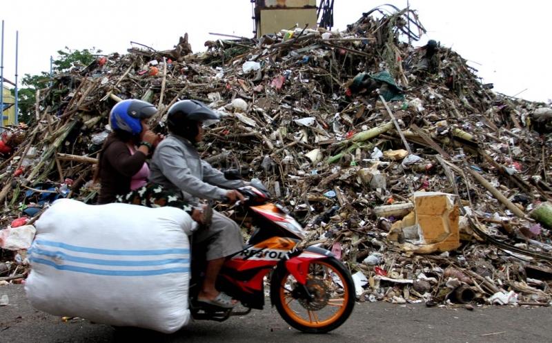 Pengendara motor melintasi tumpukan sampah yang menggunung di Pintu Air Manggarai, Jakarta Selatan, Minggu (23/12/2012). Pengerukan sampah di Pintu Air Manggarai merupakan pekerjaan rutin yang dilakukan petugas Dinas Pekerjaan Umum Pemprov DKI Jakarta, terlebih di saat musim penghujan. Ini dilakuan agar aliran air ke pintu air tidak terganggu oleh tumpukan sampah.
