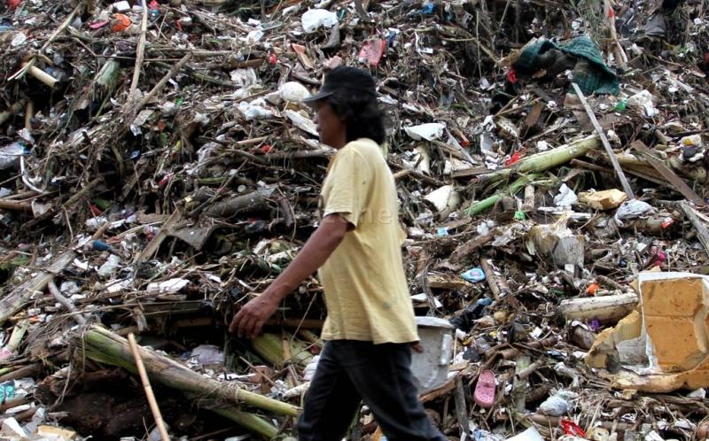 Seorang warga melintasi tumpukan sampah yang menggunung di Pintu Air Manggarai, Jakarta Selatan, Minggu (23/12/2012). Pengerukan sampah di Pintu Air Manggarai merupakan pekerjaan rutin yang dilakukan petugas Dinas Pekerjaan Umum Pemprov DKI Jakarta, terlebih di saat musim penghujan. Ini dilakuan agar aliran air ke pintu air tidak terganggu oleh tumpukan sampah.