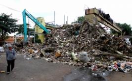 Seorang warga melintasi tumpukan sampah yang menggunung di Pintu Air Manggarai, Jakarta Selatan, Minggu (23/12/2012). Sementara di belakangnya, sebuah kendaraan berat pengeruk sampah milik Dinas Pekerjaan Umum Pemprov DKI Jakarta disiagakan. Pengerukan sampah di Pintu Air Manggarai merupakan pekerjaan rutin yang dilakukan petugas Dinas Pekerjaan Umum Pemprov DKI Jakarta, terlebih di saat musim penghujan. Ini dilakuan agar aliran air ke pintu air tidak terganggu oleh tumpukan sampah.