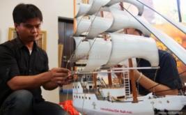 Pekerja menyelesaikan kerajinan berupa miniatur perahu Pinisi pada pameran yang menampilkan hasil industri kreatif para narapidana dari lembaga pemasyarakatan (lapas) seluruh Indonesia, di Kementerian Perindustrian, Jakarta, Kamis (24/4/2014). Pameran yang diikuti 44 peserta warga binaan dari seluruh lapas, terselenggara atas kerja sama Kemenperin dan Kemenkum HAM. Pameran ini berlangsung 22-25 April 2014.