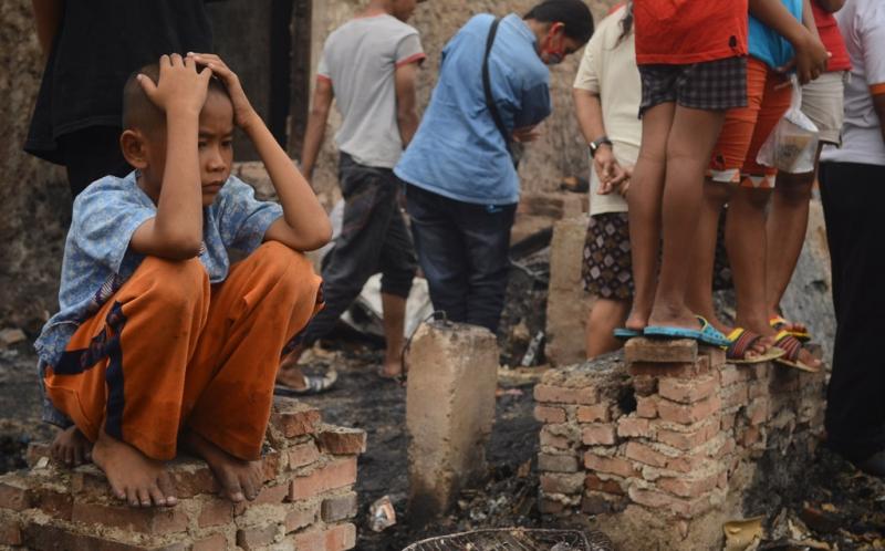Seorang anak duduk di sisa pondasi sebuah rumah setelah terjadi kebakaran di kawasan Muara Baru, Penjaringan, Jakarta Utara, Sabtu (28/6/20114). Kebakaran yang belum diketahui penyebabnya itu mengakibatkan ratusan rumah habis terbakar.