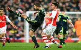 Ben Gibson mengontrol bola saat dikawal Olivier Giroud.