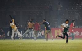Suporter Persija Jakarta melempari petugas kepolisian ketika terlibat kericuhan pada laga Torabika Soccer Championship di Stadion Utama Gelora Bung Karno, Jakarta, Jumat (24/6/2016). Pertandingan tersebut dihentikan setelah suporter Persija Jakarta masuk ke lapangan dan menyerang petugas kepolisian setelah Persija tertinggal 1-0 atas Sriwijaya FC.