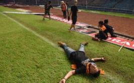 Suporter Persija Jakarta tergeletak akibat asap tembakan gas air mata ketika terlibat kericuhan dengan petugas kepolisian pada laga Torabika Soccer Championship di Stadion Utama Gelora Bung Karno, Jakarta, Jumat (24/6/2016). Pertandingan tersebut dihentikan setelah suporter Persija Jakarta masuk ke lapangan dan menyerang petugas kepolisian setelah Persija tertinggal 1-0 atas Sriwijaya FC.