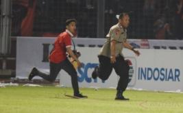 Suporter Persija Jakarta mengejar petugas kepolisian ketika terlibat kericuhan pada laga Torabika Soccer Championship di Stadion Utama Gelora Bung Karno, Jakarta, Jumat (24/6/2016). Pertandingan tersebut dihentikan setelah suporter Persija Jakarta masuk ke lapangan dan menyerang petugas kepolisian setelah Persija tertinggal 1-0 atas Sriwijaya FC.
