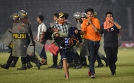 Suporter Persija Jakarta membopong rekannya ketika terjadi kericuhan dengan petugas kepolisian pada laga Torabika Soccer Championship di Stadion Utama Gelora Bung Karno, Jakarta, Jumat (24/6/2016). Pertandingan tersebut dihentikan setelah suporter Persija Jakarta masuk ke lapangan dan menyerang petugas kepolisian setelah Persija tertinggal 1-0 atas Sriwijaya FC.