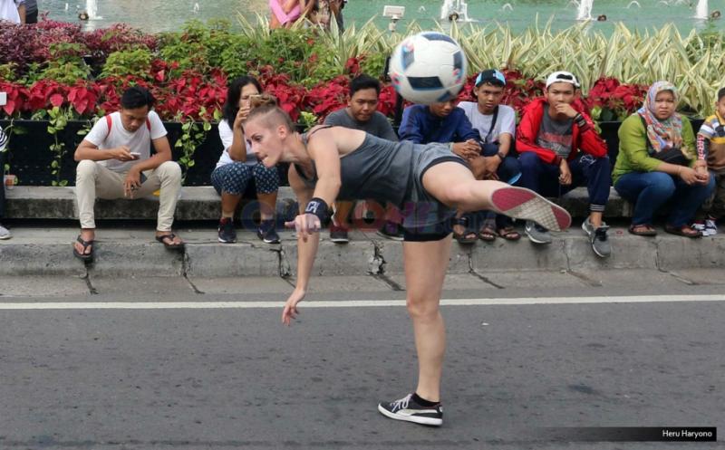 """Seorang bule perempuan melakukan aksi memainkan bola """"freestyle"""" saat Hari Bebas Kendaraan Bermotor di Bundaran Hotel Indonesia, Jakarta, Minggu (17/7/2016). Aksi bule ini menjadi pusat perhatian karena kebolehannya memainkan bola."""
