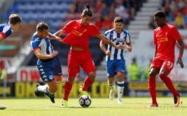 Pesepakbola Wigan Athletic Jason Pearce menarik jersey pesepakbola Liverpool Roberto Firmino.