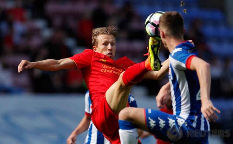 Pesepakbola Liverpool Lucas Leiva menendang bola yang mengarah ke kepala salah satu pemain Wigan Athletic.