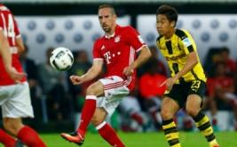 Franck Ribery (kiri) menendang bola saat dikawal Shinji Kagawa.