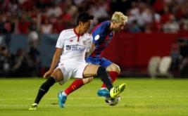Hiroshi Kiyotake (kiri) berusaha merebut bola dari kaki Lionel Messi.