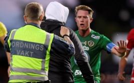 Petugas berusaha mengamankan seorang pria tidak dikenal yang masuk ke lapangan dan menyerang kiper Ostersunds, Aly Keita, saat laga Ostersunds kontra Jonkoping Sodra, di Jonkoping, Swedia, Senin (15/8/2016).