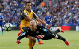 Penjaga gawang Arsenal Kasper Schmeichel menyundul bola untuk mengamankan tendangan pemain Arsenal Alexis Sanchez pada premier League di King Power Stadium Sabtu atau Minggu (21/8/2016).  Arsenal bermain imbang tanpa gol dengan Leicester City.