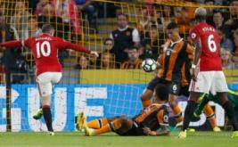 Wayne Rooney (kiri) menendang bola ke arah gawang Hull City.