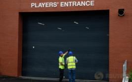Dua pekerja memperhatikan salah satu bagian dari Stadion Anfield, Inggris. Kandang baru The Reds ini kabarnya mampu menampung penonton menjadi 54.000.