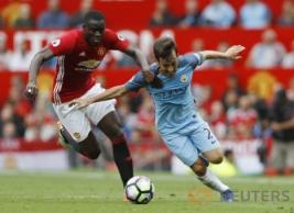 """David Silva saat berebut bola dengan Eric Bailly pada pertandingan Manchester United vs Manchester City di Stadion Old Trafford, Inggris, Sabtu (10/9/2016). Pada """"Derby Manchester"""" MU takluk di kandang sendiri dengan Skor 2-1."""
