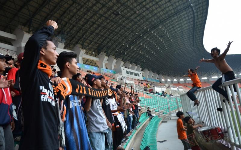 Suporter tim sepakbola DKI Jakarta meneriakkan yel-yel dukungan saat pertandingan melawan tim Jawa Tengah pada laga grup A PON XIX Jabar di Stadion Pakansari, Cibinong, Bogor, Jumat (16/9/2016). Pada laga ini, tim sepakbola Jawa Tengah mengalahkan tim DKI Jakarta lewat skor tipis 1-0.