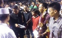 Pengasuh Pondok Pesantren Syekh Abdul Qodir al Jailani Kraksaan, KH Abdul Hafidz Aminudin (kiri) menyerahkan hadiah dan trofi kepada juara Grand Final turnamen Hary Tanoe Cup 2016.