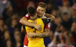 Kieran Gibbs (jersey kuning) memeluk Nicklas Bendtner usai pertandingan. Bendtner sendiri merupakan mantan pemain Arsenal.