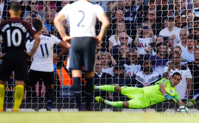 Kiper Manchester City Claudio Bravo (kanan) melakukan penyelamatan tendangan penalti Erik Lamela.