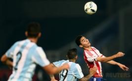 Miguel Almiron (kanan) mengontrol bola saat dikawal dua pemain Argentina.