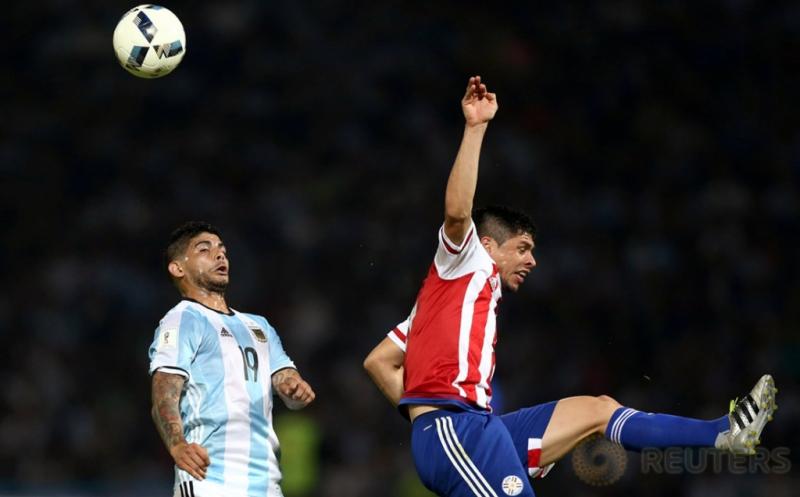 Ever Banega (kiri) saat berebut bola di udara dengan Rodrigo Rojas.