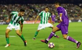 Cristiano Ronaldo (kanan) mengecoh dua pemain Real Betis.