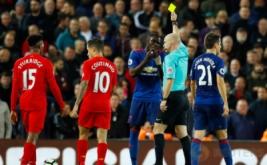 Wasit Anthony Taylor (dua kanan) memberikan kartu kuning kepada Eric Bailly (tengah) pada lanjutan Liga Inggris musim 2016-2017 di Stadion Anfield, Selasa (18/10/2016) dini hari WIB.