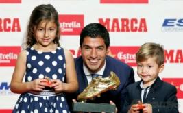 Striker Barcelona Luis Suarez bersama anaknya Delfina dan Benjamin, berpose dengan sepatu emas di Barcelona, Spanyol, Kamis (20/10/2016). Suarez berhak atas sepatu emas karena menjadi pencetak gol terbanyak di Eropa musim lalu. Bersama Barca, Suarez mencetak 40 gol di La Liga musim lalu.