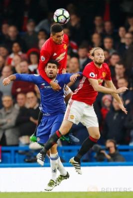 Diego Costa (kiri bawah) berebut bola dengan dua pemain Manchester United Daley Blind (kanan) dan Chris Smalling.
