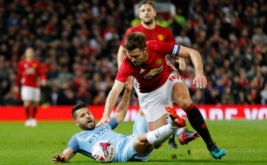 Sergio Aguero (bawah) terjatuh saat berebut bola dengan Michael Carrick.