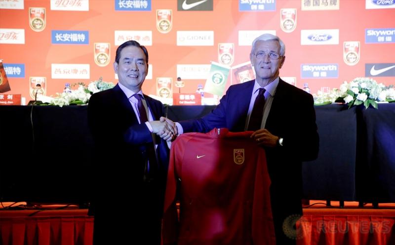 Marcello Lippi (kanan)  menerima jersey timnas China dari Presiden Asosiasi Sepakbola China (CFA) Cai Zhenhua dalam konferensi pers di Beijing, China, Jumat (28/10/2016). CFA resmi menunjuk Macello Lippi sebagai pelatih timnas China. (REUTERS/Jason Lee)