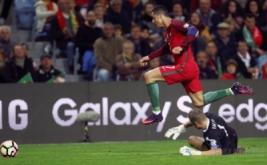 Cristiano Ronaldo (atas) melewati Kiper Latvia Andris Vanins. (REUTERS/Pedro Nunes)