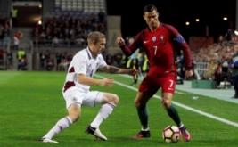 Cristiano Ronaldo (kanan) berusaha melewati Gints Freimanis. (REUTERS/Pedro Nunes)