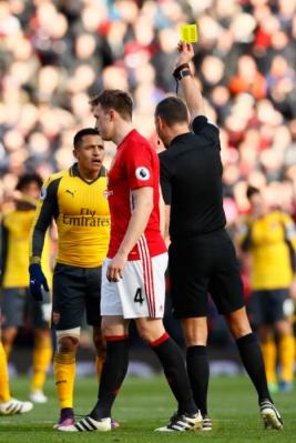 Wasit Andre Marriner (kanan) memberikan kartu kuning kepada Alexis Sanchez. (Reuters/Jason Cairnduff Livepic)