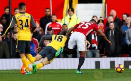 Antonio Valencia (kanan) dan Nacho Monreal (tengah) sama-sama terjatuh di kotak penalti Arsenal. Wasit tidak menunjuk ini sebagai pelanggaran sehingga tidak memberikan hadiah penalti untuk Manchester United. (Reuters/Jason Cairnduff Livepic)