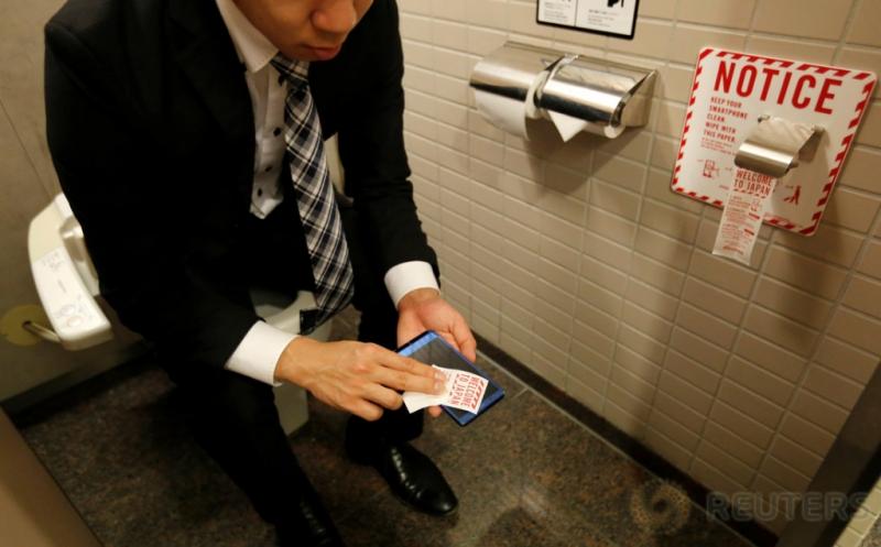 Seseorang menggunakan kertas pembersih ponsel saat berada di dalam toilet di Bandara Internasional Narita, Jepang, Rabu (28/12/2016). (REUTERS/Toru Hanai)