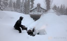 Seorang pria sedang berusaha menyingkirkan salju dengan traktor di jalan yang mengarah ke rumahnya di Incline Village, Nevada, Amerika Serikat, Kamis (12/1/2017) WIB. Salju yang melanda Amerika menutupi jalan dan rumah warga.