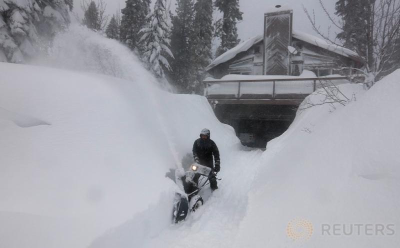 Seorang Pria sedang membersihkan tumpukan salju di halaman rumahnya di Incline Village, Nevada, Amerika Serikat (12/1/2017)WIB. Salju yang melanda Amerika menutupi jalan dan rumah warga.