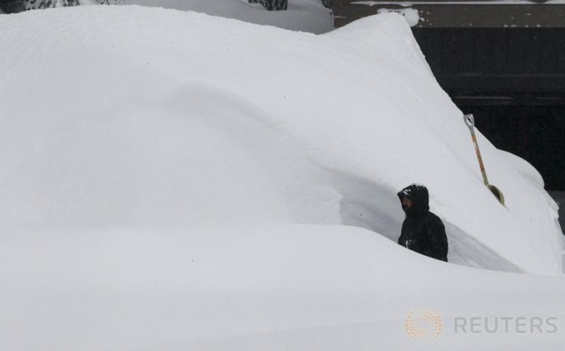 Seorang Pria melintas di antara tumpukan salju di Incline Village, Nevada, Amerika Serikat (12/1/2017)WIB. Salju yang melanda Amerika menutupi jalan dan rumah warga.